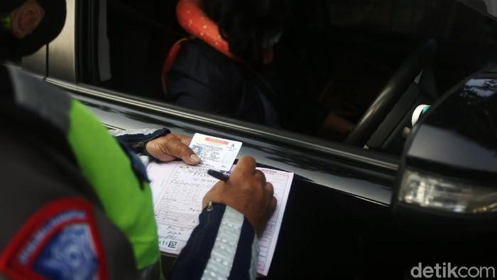 Petugas Polisi Lalu Lintas (Polantas) Satlantas Polres Jakarta Timur saat melakukan penilangan pada pengendara mobil yang melanggar aturan Ganjil-Genap di Simpang Cawang, Jakarta Timur, Senin (10/8/2020). Sanksi tilang bagi pelanggar pembatasan kendaraan bermotor berdasarkan nomor polisi ganjil dan genap diberlakukan lagi di Jakarta mulai hari ini. Pembatasan itu sebelumnya dicabut sementara sejak pertengahan Maret lalu karena adanya pandemi Covid-19 yang berujung pada penerapan pembatasan sosial berskala besar (PSBB).