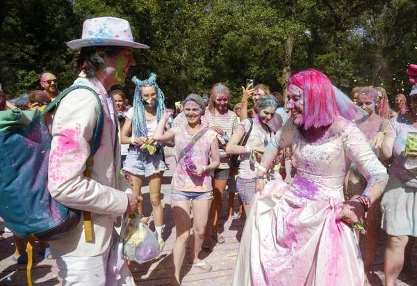 Orang-orang melemparkan bubuk berwarna ke pengantin perempuan dan laki-laki, Maria dan Andrew, selama Festival Holi.