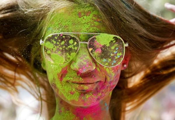 Seorang wanita tersenyum saat wajahnya ditutupi dengan bedak berwarna selama Festival Holi di Kyiv, Ukraina.