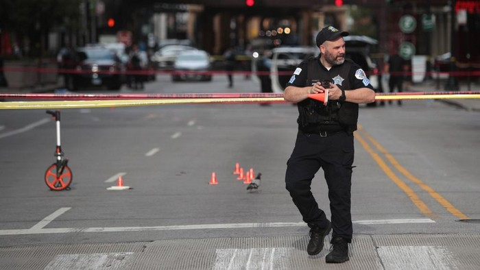 CHICAGO, ILLINOIS - AUGUST 10: Police investigate where a shooting took place on Michigan Ave. hours after the city suffered from widespread looting and vandalism, on August 10, 2020 in Chicago, Illinois. Police made several arrests during the night of unrest and recovered at least one firearm.   Scott Olson/Getty Images/AFP