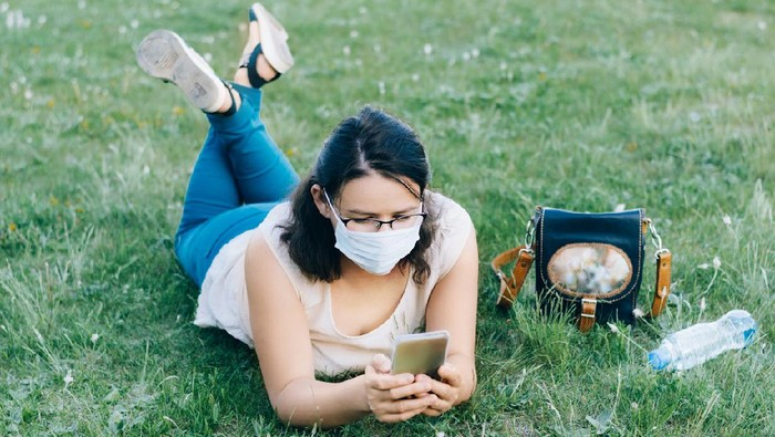 Young woman in a protective mask lies on green grass. New normal walk in City park during coronavirus pandemic.
