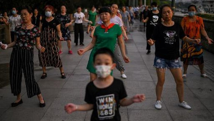 This photo taken on August 4, 2020 shows people dancing during the afternoon next to the Yangtze River in Wuhan in Chinas central Hubei province. - The citys convalescence since a 76-day quarantine was lifted in April has brought life and gridlocked traffic back onto its streets, even as residents struggle to find their feet again. Long lines of customers now stretch outside breakfast stands, a far cry from the terrified crowds who queued at city hospitals in the first weeks after a city-wide lockdown was imposed in late January to curb the spread of the COVID-19 coronavirus. (Photo by Hector RETAMAL / AFP)