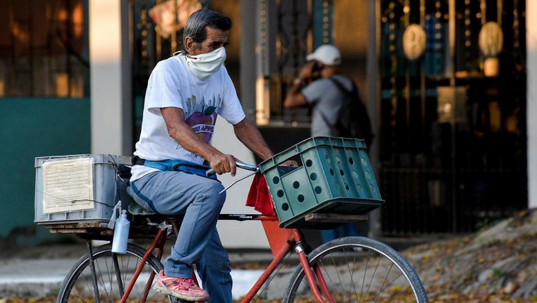 A man wearing a face mask rides on his bicycle along a street of Havana, on July 29, 2020. - Cuba has 2588 confirmed cases of COVID-19 and 87 deceased. (Photo by YAMIL LAGE / AFP)