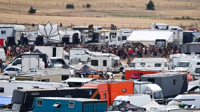 People gather with their tents, vehicles and camping cars, for a rave party, on an agricultural land in Causse Mejean, in the heart of the Cevennes National Park, southern France on August 10, 2020, despite the limitation of gatherings linked to COVID-19, the novel coronavirus. - The rally gathered up to 10,000 people announced the prefecture of Lozere. Starting from August 9, 2020 at 8:00 am, the gendarmes had blocked the access to prevent other people from joining the party where there were also very young children, according to the prefect. Two Covid-19 screening centers are being set up in transit areas, near the site, to be operational on Tuesday morning, also said Ms. Hatsch. (Photo by Pascal GUYOT / AFP)