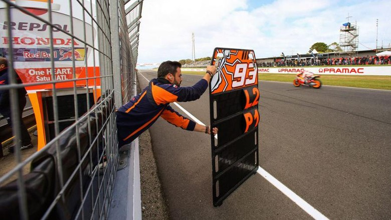 Mekanik tim balap sedang menunjukkan papan pit board