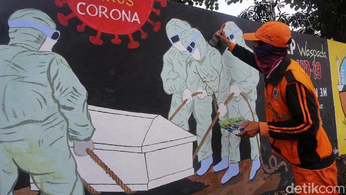 Petugas Pekerja Penanganan Sarana dan Prasarana Umum (PPSU) Kelurahan Bukit Duri, Jakarta menyelesaikan pembuatan mural tentang Covid-19, Jakarta, Selasa  (11/8/2020). Jumlah pasien positif Covid-19 di DKI Jakarta per Senin (10/8/2020) adalah 26.162 orang. Angka ini tertinggi di Indonesia. Dari total kasus positif itu, 16.446 orang dinyatakan telah sembuh, sedangkan 940 orang dilaporkan meninggal dunia. Sementara itu, sebanyak 8.807 pasien masih menjalani perawatan di rumah sakit maupun menjalani isolasi mandiri.
