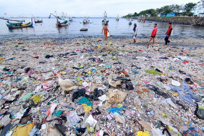 Nelayan berjalan di antara tumpukan sampah di Pelabuhan Muncar, Banyuwangi, Jawa Timur, Selasa (11/8/2020). Menurut warga sekitar, sampah yang menumpuk di sepanjang pantai akibat banjir besar pada tahun 2014 itu, juga diperparah oleh kebiasaan warga yang membuang sampah di tempat itu. ANTARA FOTO/Budi Candra Setya/hp.