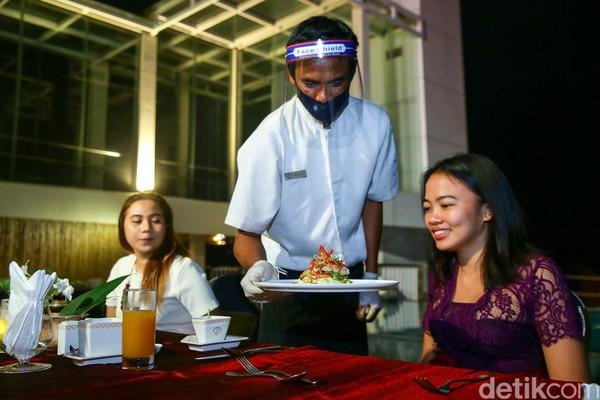 Sembari menikmati angin malam, beberapa hidangan andalan restoran tersebut disajikan oleh pelayanan yang mengenakan masker, face shield, dan sarung tangan.