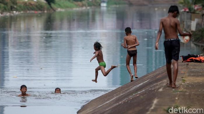 Sejumlah anak-anak memanfaatkan aliran Sungai Ciliwung untuk bermain dan berenang. Meski kotor, mereka tetap terlihat semringah.