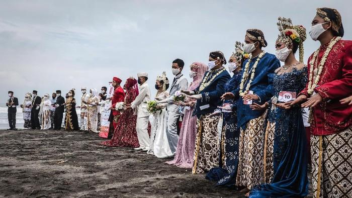 Momen pernikahan massal dalam rangka HUT RI digelar di pantai Cemara Sewu, Yogyakarta. Wajah semringah terpancar dari para pasangan.