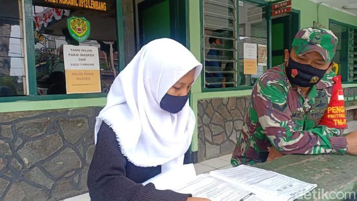 Seorang siswa memanfaatkan WiFi gratis di Koramil Lembang.