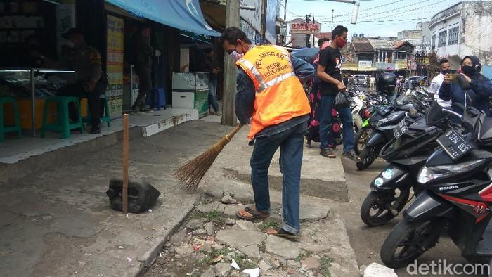 Tak kenakan masker, warga di Cimahi dihukum bersih-bersih.