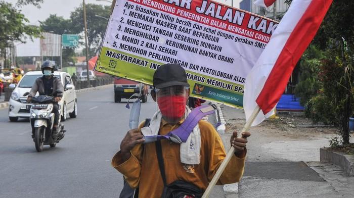 Ujun Junaedi (59) melakukan aksi jalan kaki dari Subang menuju Jakarta saat melintas di Jalan Sultan Agung, Bekasi, Jawa Barat, Jumat (7/8/2020). Aksi jalan kaki menuju Istana Presiden tersebut untuk mensosialisasikan hidup bersih dan sehat kepada masyarakat agar terhindar dari wabah COVID-19. ANTARA FOTO/Fakhri Hermansyah/wsj.