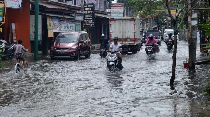 Sejumlah pengendara motor melintasi banjir yang menggenangi Jalan Raya Jatimulya, Kabupaten Bekasi, Jawa Barat, Kamis (13/8/2020). Menurut pengakuan warga, jalan raya dan perumahan di wilayah tersebut selalu terendam banjir walau intensitas hujan ringan akibat sistem drainase yang buruk dan berkurangnya resapan air dampak pembangunan di wilayah Bekasi. ANTARA FOTO/Suwandy/aww.