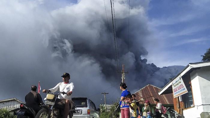 Pengendara melintas di Jalan Karo-Langkat dengan latar belakang Gunung Sinabung yang menyemburkan material vulkanik di Desa Kutarayat, Naman Teran, Karo, Sumatera Utara, Kamis (13/8/2020). Pusat Vulkanologi dan Mitigasi Bencana Geologi (PVMBG) menyatakan Gunung Sinabung berstatus level III atau siaga dan meminta masyarakat untuk tidak melakukan aktivitas di desa yang telah direlokasi. ANTARA FOTO/Sastrawan Ginting/Lmo/wsj.