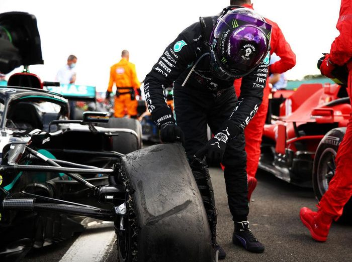 NORTHAMPTON, ENGLAND - AUGUST 02: Race winner Lewis Hamilton of Great Britain and Mercedes GP inspects his punctured tyre in parc ferme during the F1 Grand Prix of Great Britain at Silverstone on August 02, 2020 in Northampton, England. (Photo by Bryn Lennon/Getty Images)