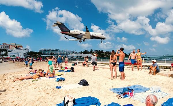 Turis-turis berdiri di sekitar tepi pantai, menanti pesawat lewat dan merekam momen-momen burung besi itu melintas di atas kepala dengan ponsel atau kamera. (iStock)