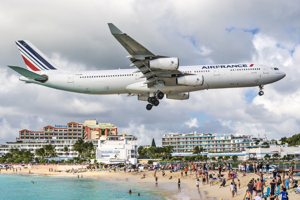 Walaupun pesawat terbang begitu rendah, turis yang wisata di Pantai Maho tidak lantas mengosongkan wilayah pantai. (iStock)
