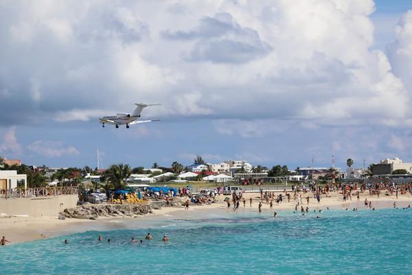 Para wisatawan tak sedikit yang berteriak dan bersorak girang ketika pesawat melintas dengan begitu rendahnya di depan mata. Menyaksikan langsung pesawat yang akan mendarat dari dekat ini memang seru, tapi sebenarnya cukup berbahaya. (iStock)