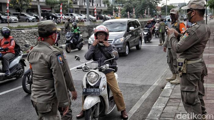 Sejumlah petugas Satpol PP tingkat kota melakukan razia pendisiplinan pemakaian masker di kawasan Danau Sunter, Jakarta Utara, Rabu (13/8). Kegiatan tersebut bertujuan memberikan ketegasan kepada para pengendara yang tidak tertib memakai masker di masa PSBB Transisi ini.
