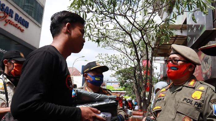 Petugas tegur warga yang tidak menggunakan masker.