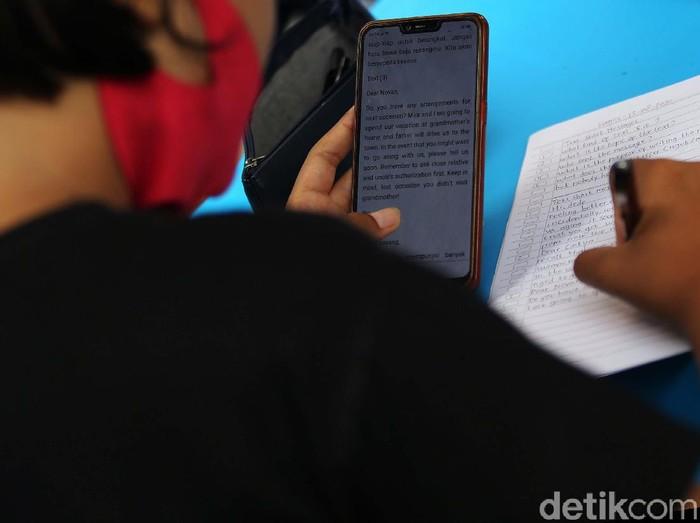 Warga Pondok Kelapa, Jakarta Timur gotong royong membangun tenda pintar. Di tenda ini pelajar mendapat WiFi gratis untuk belajar online.