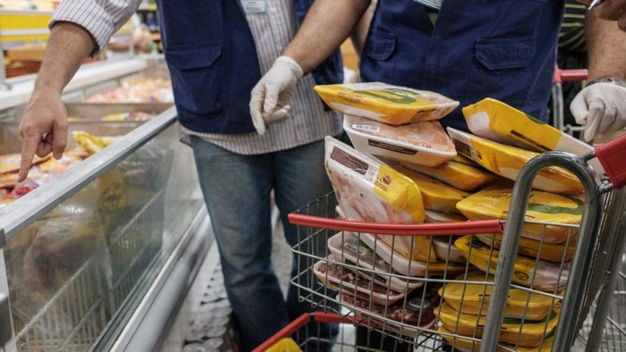 The staff of Rio de Janeiro states consumer protection agency, PROCON, inspect and remove chicken products that are not frozen from a freezer at a supermarket in Rio de Janeiro, Brazil, on March 24, 2017. - Brazil, the worlds biggest beef and poultry exporter, has been hit by allegations of corrupt practices in its meat industry. Police have halted exports by 21 meat processers suspected of bribing inspectors to issue them bogus health certificates for rotten meat. (Photo by Yasuyoshi Chiba / AFP)