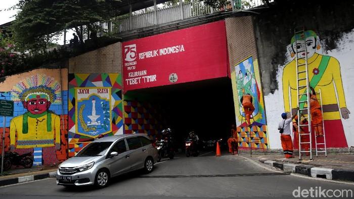 Kolong jembatan Stasiun Cawang terlihat berbeda dari biasanya. Petugas PPSU mempercantik kawasan tersebut dengan cat warna-warni yang ciamik. Penasaran?