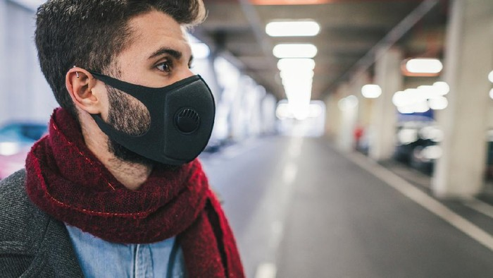 Side view image of young man wearing anti-smog mask for health and lungs protection in the city. City pollution concept