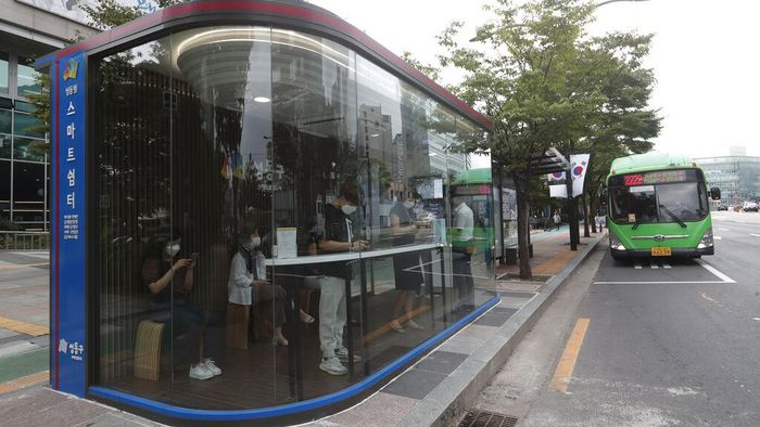 A bus shelter designed to block people with fever amid a spread of the coronavirus, is installed at a bus stop in Seoul, South Korea, Friday, Aug. 14, 2020. The glass panels-covered bus stops at a Seoul district, are equipped with thermal cameras that screen people for fevers and also automatic doors that doesn't let in any one with high temperatures. (AP Photo/Ahn Young-joon)