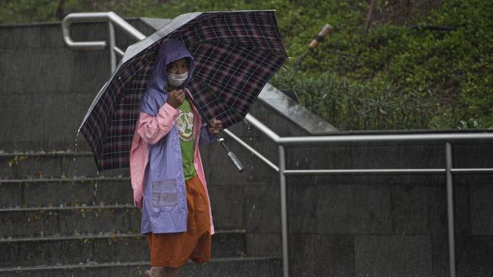 Warga menggunakan payung saat hujan mengguyur Stasiun MRT Dukuh Atas BNI, Jakarta, Kamis (13/8/2020). Berdasarkan data Badan Meteorologi, Klimatologi dan Geofisika ( BMKG), meski puncak kemarau terjadi pada Agustus ini, sebagian wilayah Jabodetabek diguyur hujan dengan intensitas ringan hingga sedang karena adanya fenomena gelombang atmosfer (Rossby Ekuator) di wilayah Indonesia bagian barat. ANTARA FOTO/Aditya Pradana Putra/aww.