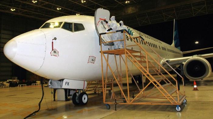 Pekerja Garuda Maintenance Facility (GMF) dengan menggunakan alat pelindung diri (APD) lengkap melakukan penyemprotan cairan disinfektan pada bagian pesawat Garuda Indonesia di Hanggar GMF AeroAsia Bandara Soekarno Hatta, Tangerang, Banten, Kamis (13/8/2020). Hal tersebut dilakukan sebagai upaya memutus mata rantai penyebaran COVID-19. ANTARA FOTO/Muhammad Iqbal/aww.