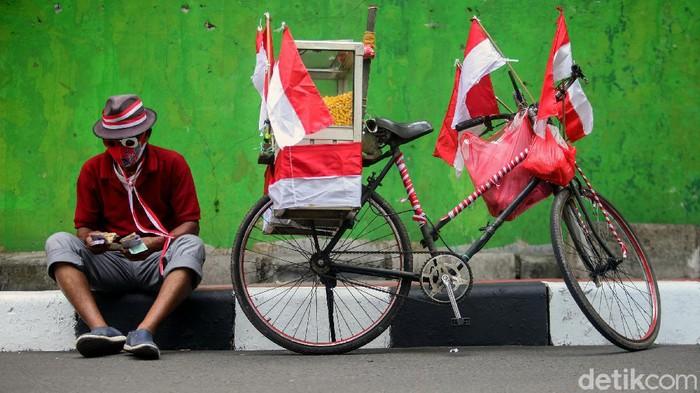Semarak perayaan Hari Kemerdekaan membuat Tarjono, pedagang jagung manis, antusias hias sepeda dagangannya. Tarjono hias sepedanya dengan atribut merah putih.