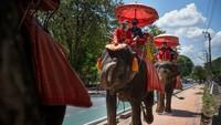Turis Thailand memakai masker saat menunggangi gajah di Istana Gajah Ayutthaya dan Royal Kraal di Ayutthaya, Thailand.