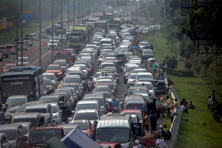 Kepadatan terlihat di jalur puncak Bogor saat masa libur panjang. Tak sedikit wisatawan yang memilih keluar dari kendaraannya sembari menunggu kemacetan reda.