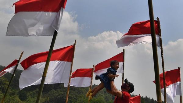 Pengunjung bermain bersama anaknya di antara bendera Merah Putih yang dipasang di Poetoek Suko, Trawas, Mojokerto, Jawa Timur, Minggu (16/8/2020).
