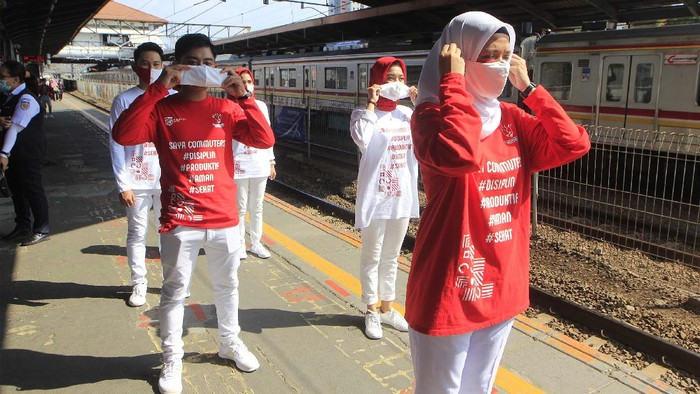 Sekelompok milenial PT KCI bernama C-Ranger berkontum merah putih mensosialisasikan penggunaan masker di Stasiun Tanah Abang,