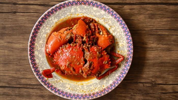 Crab in Padang sauce or Padang crab (Indonesian: Kepiting saus Padang) on wood background.