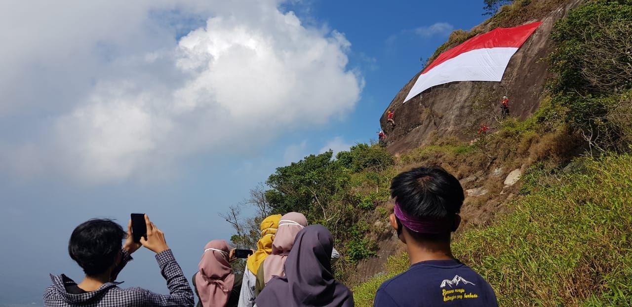 Merayakan HUT RI ke-75 sebuah bendera Merah Putih raksasa dibentangkan di tebing Gunung Bongkok, Purwakarta. Seperti apa?