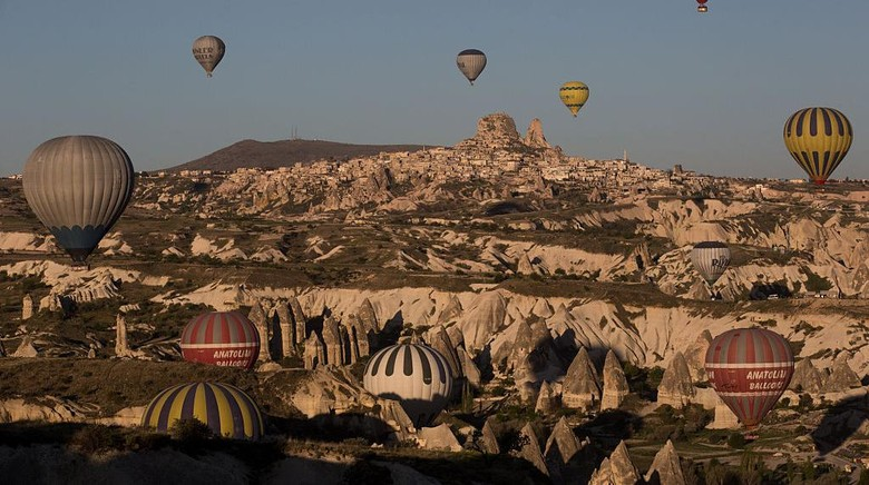 NEVSEHIR, TURKEY - APRIL 18: Tourists look out at the view above a cave hotel on April 18, 2016 in Nevsehir, Turkey. Cappadocia, a historical region in Central Anatolia dating back to 3000 B.C is one of the most famous tourist sites in Turkey. Listed as a World Heritage Site in 1985, and known for its unique volcanic landscape, fairy chimneys, large network of underground dwellings and some of the best hot air ballooning in the world, Cappadocia is preparing for peak tourist season to begin in the first week of May.  Despite Turkeys tourism downturn, due to the recent terrorist attacks,  internal instability and tension with Russia, local vendors expect tourist numbers to be stable mainly due to the unique activities on offer and unlike other tourist areas in Turkey such as Antalya, which is popular with Russian tourists, Cappadocia caters to the huge Asian tourist market.  (Photo by Chris McGrath/Getty Images)