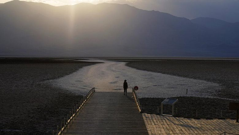 A person walks on a boardwalk at the salt flats at Badwater Basin, Monday, Aug. 17, 2020, in Death Valley National Park, Calif. Death Valley recorded a scorching 130 degrees (54.4 degrees Celsius) Sunday, which if the sensors and other conditions check out, would be the hottest Earth has been in more than 89 years and the third-warmest ever measured. (AP Photo/John Locher)