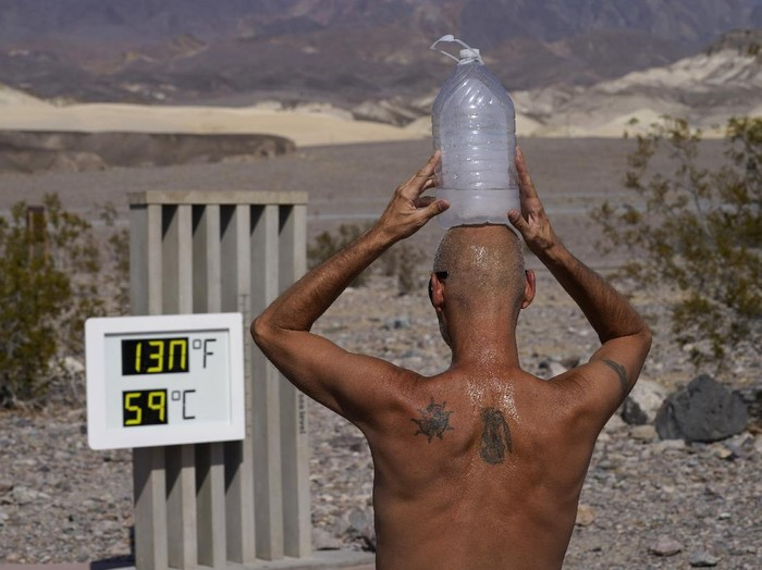 Steve Krofchik cools off with a bottle of ice water on his head Monday, Aug. 17, 2020, in Death Valley National Park, Calif. Death Valley recorded a scorching 130 degrees (54.4 degrees Celsius) Sunday, which if the sensors and other conditions check out, would be the hottest Earth has been in more than 89 years and the third-warmest ever measured. (AP Photo/John Locher)