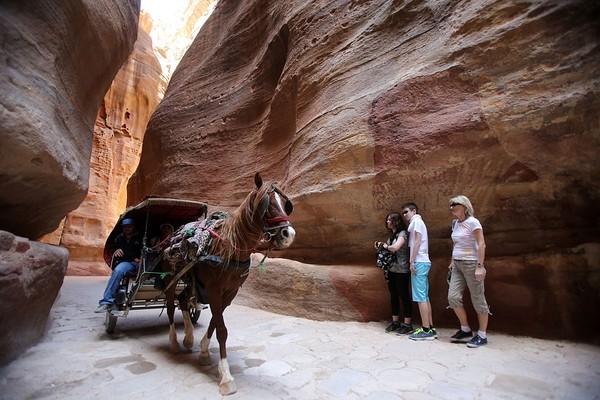 Petra adalah sebuah kota kuno yang hampir seluruh bangunannya terpahat di dinding tebing. Salah satunya adalah terowongan ngarai yang biasa disebut Siq. Di sana, Anda bisa melihat pahatan di dinding batu, seperti pipa dari tanah liat yang dulu digunakan dalam sistem pengairan. Jordan Pix/Getty Images