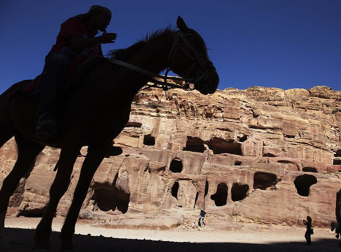 PETRA, JORDAN- APRIL 3: Tourists watch a horse pull a carriage as they visit the legendary Petra, Jordans most famous tourist attraction on April 3, 2015 in Petra, Jordan. Stakeholders have put together an urgent marketing plan to salvage the Kingdoms tourism industry by promoting national tourist products in new and traditional markets worldwide, according to Tourism Minister Nayef Al Fayez. Visits to Jordan and its famous archeological site of Petra have plummeted because of unrest in the broader Middle East, and discounts on airfare and tours to the country have yet to bring visitor numbers back to levels seen in years past. The number of Arab tourists has not been affected by the regional turmoil, but the number of visitors to archaeological sites has recently dropped and those who visit these sites are mostly non-Arabs. (Photo by Jordan Pix/ Getty Iimages)