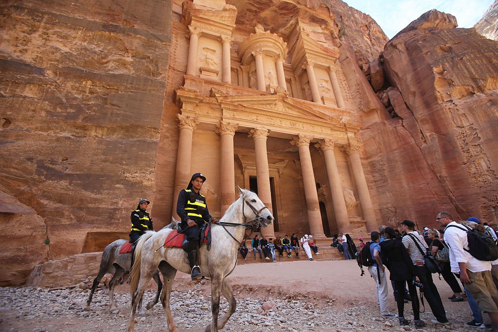 PETRA, JORDAN- APRIL 3: Tourists watch a horse pull a carriage as they visit the legendary Petra, Jordan's most famous tourist attraction on April 3, 2015 in Petra, Jordan. Stakeholders have put together an urgent marketing plan to 'salvage' the Kingdom's tourism industry by promoting national tourist products in new and traditional markets worldwide, according to Tourism Minister Nayef Al Fayez. Visits to Jordan and its famous archeological site of Petra have plummeted because of unrest in the broader Middle East, and discounts on airfare and tours to the country have yet to bring visitor numbers back to levels seen in years past. The number of Arab tourists has not been affected by the regional turmoil, but the number of visitors to archaeological sites has recently dropped and those who visit these sites are mostly non-Arabs. (Photo by Jordan Pix/ Getty Iimages)