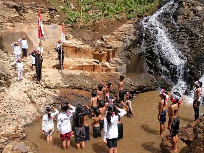 Sejumlah warga mengikuti upacara bendera di Curug Tarung kawasan lereng gunung Prahu Dusun Gunung Wuluh, Canggal, Candiroto, Temanggung, Jawa Tengah, Selasa (18/8/2020). Upacara yang dilaksanakan di lokasi jalur perjuangan Pangeran Diponegoro tersebut untuk memperingati HUT ke-75 Kemerdekaan Indonesia sekaligus untuk mempromosikan wisata alam yang baru ditemukan oleh warga. ANTARA FOTO/Anis Efizudin/pras.