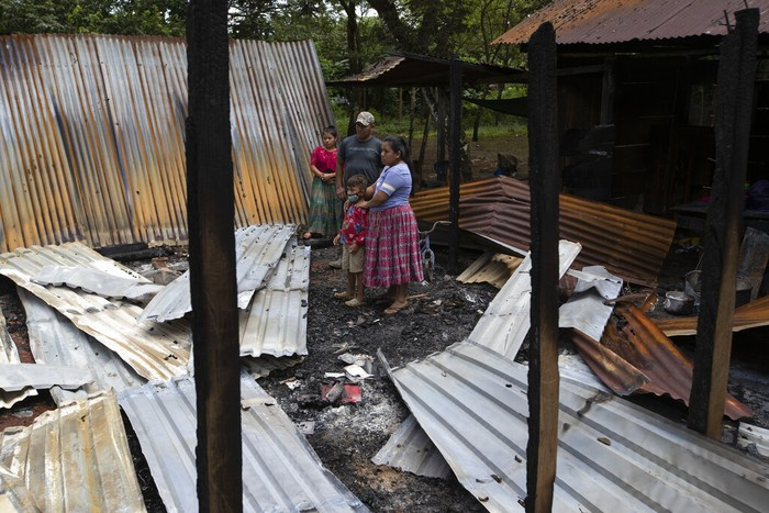 Floricelda Cucul, front right, stands with her husband Celestino Bol and children in the rubble of their shack home burned down by unidentified, armed men, as she returns days after the attack to see what remains where they live on a coffee plantation in Cubilguitz, Guatemala, Tuesday, Aug. 18, 2020. Indigenous families have been living here for years as the result of a long-running labor dispute, and on Monday, President Alejandro Giammattei said the attackers had been identified. (AP Photo/Moises Castillo)