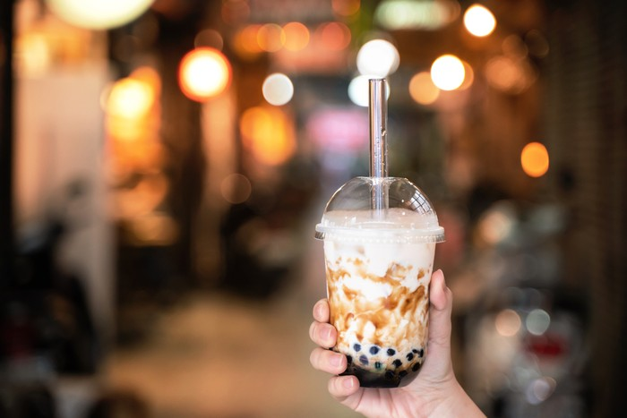Young girl in denim jacket is drinking brown sugar flavored tapioca pearl bubble milk tea with glass straw in night market of Taiwan, close up, bokeh