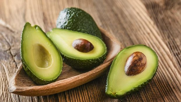 Avocado on old wooden table in bowl. Halfs of avocados fresh fruits healthy food.