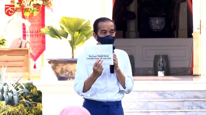 Presiden Joko Widodo (Jokowi) membagikan batuan modal kerja kepada para pedagang di Istana Merdeka, Jakarta. Total bantuan yang diberikan Rp 2,4 juta.